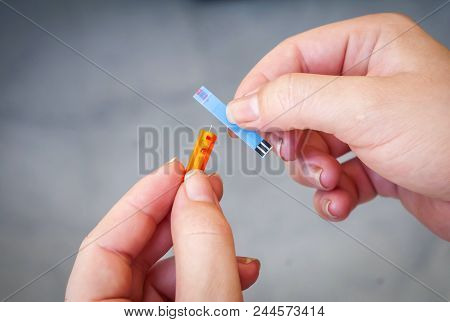 Woman Patient With Pregnancy Diabetes Holding In Her Hands An Orange Glucometer Needle With Blood St