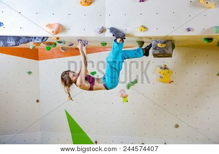 Young Athletic Woman Climbing Upside Down In Bouldering Gym