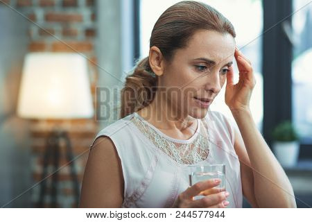 Severe Migraine. Sick Mature Woman Touching Head While Carrying Glass Of Water