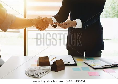 Image Of Real Estate Broker Agent And Customer Shaking Hands And Give Keys After Signing Contract Do