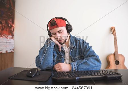 Sleeping Bearded Gamer Sitting At The Computer And Falling Asleep. A Porter Of A Tired Gamer On A Co