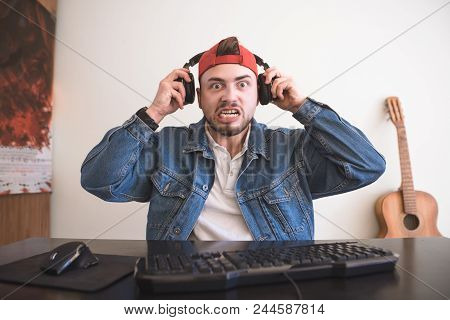 Angry Gamer With A Beard And Headphones Sitting At Home At The Computer And The Cruel Eyes Looking I