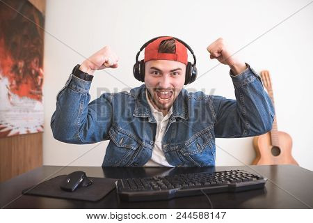 Happy Adult Gamer With A Beard Sitting At Home On A Computer And Rejoicing. Joyful Man With Headphon
