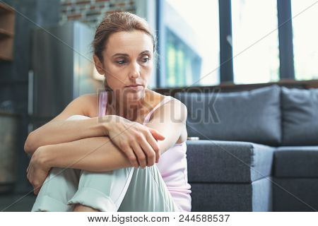 Depression mood. Miserable mature woman looking aside and hugging knees poster