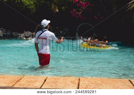 Back View On Lifeguard Who Shows Stop Sign For Kids Floating On Pontoon.