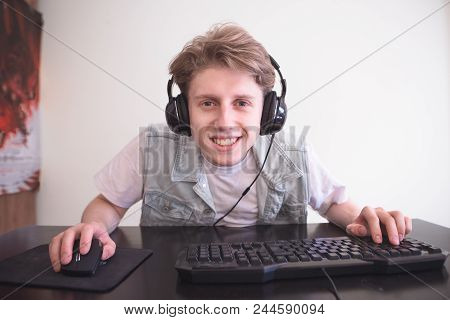 Happy Young Gamer With Headphones Plays Computer Games At Home And Smiles. Portrait Of A Smiling Tee