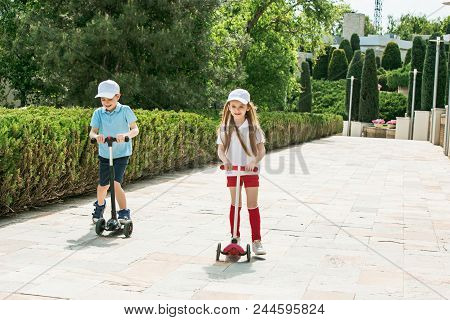 Preschooler Girl And Boy Riding Kick Scooter Outdoors. Happy Cute Little Children Playing On The Str