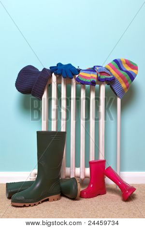 Photo of childrens hats, gloves and wellies boots drying by an old traditional cast iron radiator in the hallway, good image for childhood winter related themes.