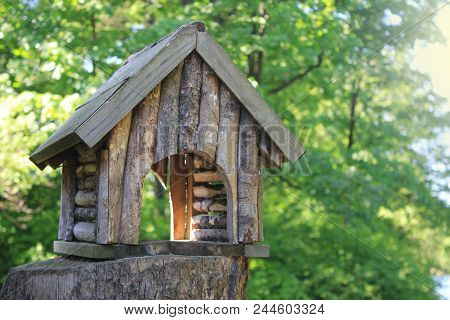 Wooden Small Tree House At The Summer Forest Landscape Background. Tree House And Bird Feeder Isolat