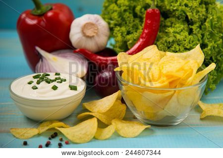 Crispy Potato Chips In A Glass Bowl With Chili Peper, Garlic, Salad  And Onions, Sour Cream On Old B