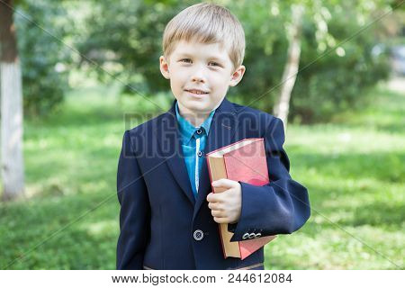 A Boy With A Book In His Hand. The Boy Is Reading A Book In The Open Air. The Boy Is Holding A Book.
