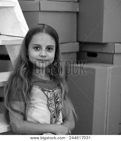 Moving In Or Out Concept. Girl With Fair Wavy Hair On Room Or Warehouse Background. Kid Stands By Pi