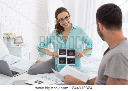 Baby In Belly. Vigorous Pregnant Woman Holding Ultrasound While Man Looking At Her