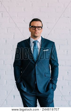 Confident Middle Aged Businessman In Suit And Eyeglasses Standing With Hands In Pockets And Looking