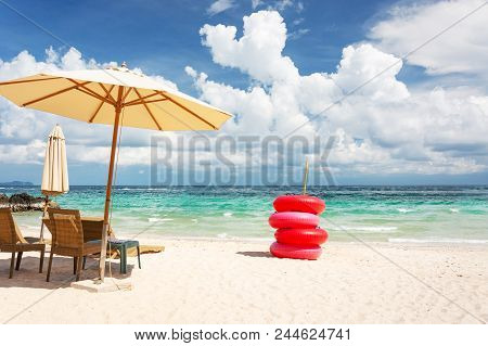 Beach Chair, Umbrella And Red Life Buoy On The Beach And The Bright Green Sea, On A Good Day.
