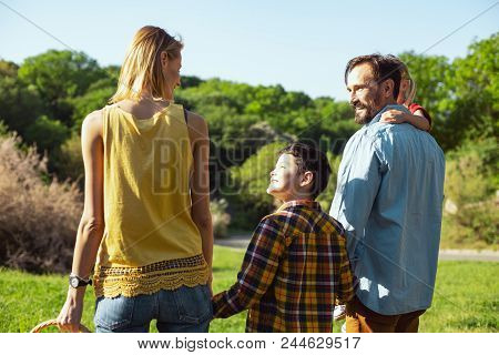 Best Parents. Cheerful Dark-haired Boy Walking With His Parents And Sister And Smiling