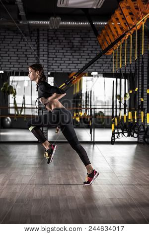 Beautiful Fitness Woman Training With Trx Fitness Straps. Suspension Exercising In Gym