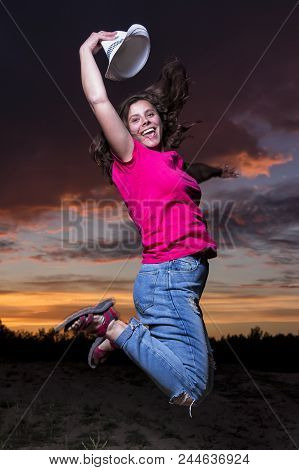 Portrait Of Happy Smiling Girl Jumping In The Evening Against Colorful Sky Background With Clouds At