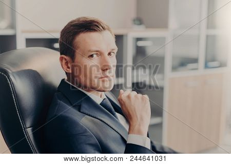 Professional Male Manager In Formal Suit, Looks Directly At Camera, Rests In Chair At Work Place, Co