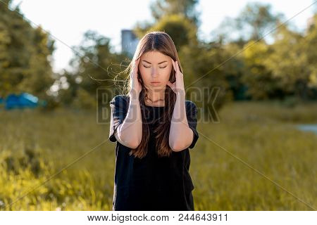 Girl Brunette In Fresh Air. Holds His Hands Around His Head. Headache. Tries To Concentrate. Migrain