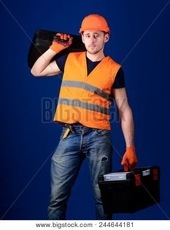 Man In Helmet, Hard Hat Holds Toolbox And Suitcase With Tools, Blue Background. Equipped Repairman C