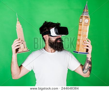 Man With Beard In Vr Glasses, Green Background. Guy In Vr Glasses Holds Big Ben And Empire State Bui
