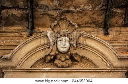 Mascaron Ornament Is A Face. Ornament The Face On The Old House. Ancient Bas-relief Face