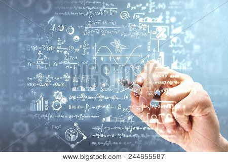 Male Hand Writing Mathematical Formulas On Blurry Background. Science And Algebra Concept. Double Ex