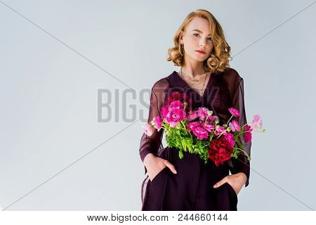 Beautiful Young Woman With Tender Pink Flowers Standing With Hands In Pockets And Looking At Camera