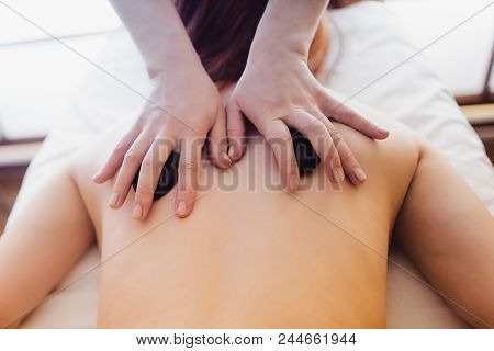 Beautiful Woman Having Hot Stones On Her Back In Spa Salon. Concept Of Healthcare And Female Beauty.