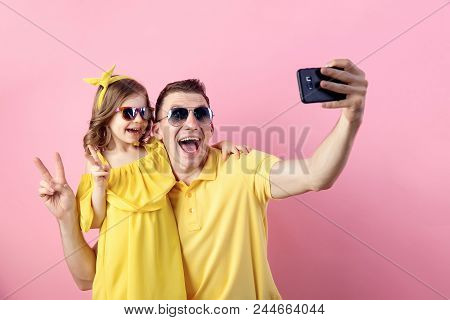 Portrait Of Happy Family Of Two People In Yellow. Daddy And Little Daughter Doing Selfie With Smartp