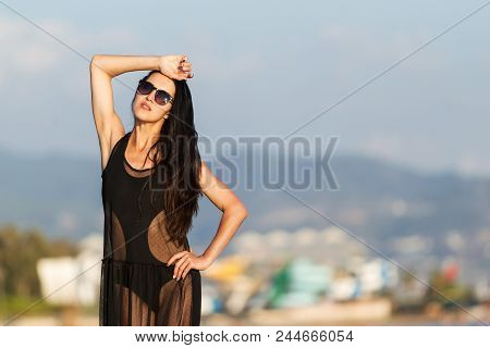 Beauty Young Woman With Long Dark Hair In Black Swimwear And Transparent Dress. Concept Of Happy Hol