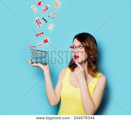 Portrait Of Beautiful Young Woman With Shopping Cart On The Wonderful Blue Studio Background And Wit