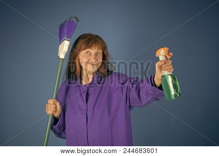 Cleaning services. Cleaning and purity. Old lady cleaner with broom on blue background. Cleanup and order services. Housekeeper woman in uniform with clean spray. Woman with long hair hold soup bottle. poster