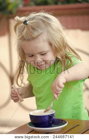 Boy With Cappuccino. Boy Child Mixing Sugar In Blue Cup. Little Kid Boy Making Tea. Childhood And Ba