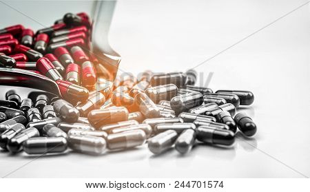 Red And Grey Capsule Pills On Stainless Steel Drug Tray And Gray Capsules On White Background. Migra