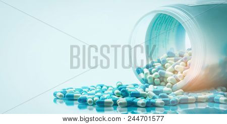 Blue And White Capsules Pill Spilled Out From White Plastic Bottle Container. Global Healthcare Conc
