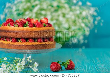 Homemade Strawberry Cake On A Glass Stand On The Blue Background. Selective Focus.