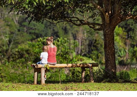 Mother, Little Baby Son Have Fun Outdoors, Sit On Bench Under The Tree On Sunny Lawn. Happy Family L