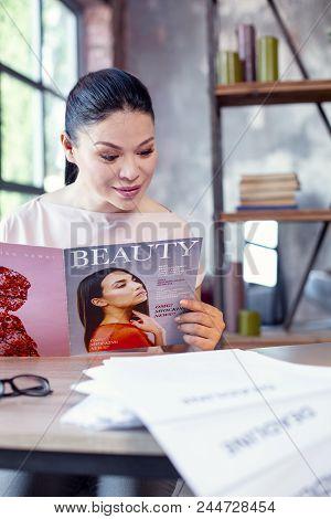 Magazine About Beauty. Positive Female Employee Posing On Blurred Background While Reading Magazine