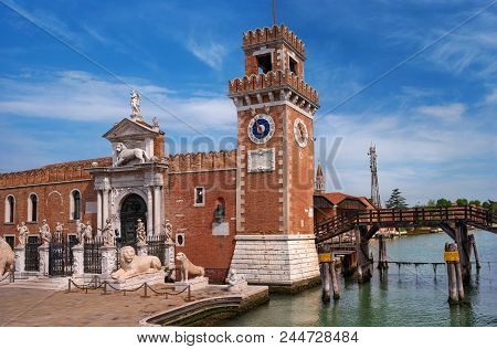 Historic shipyard, Arsenal, gate and the channel. Venice, Italy. The gate is richly decorated with sculptures. bove the gate is a sculpture of a Venetian lion. There's a clock on the tower. poster