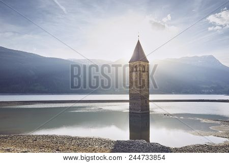 Old Church Tower In Water At Sunset. Resia Lake (lago Di Resia Or Reschensee) In South Tyrol, Italy.