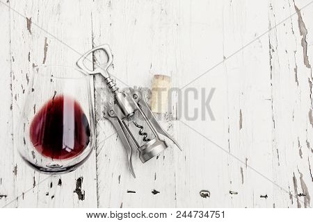 Wine Degustation Concept -  Red  Wine  Glass, Wine Corks  And Corkscrew On White Wooden Table With C