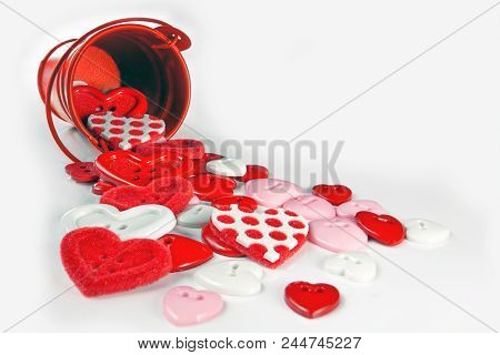 Red Hearts Buttons Spill Out Of The Bucket. The Concept Of Love Sewing