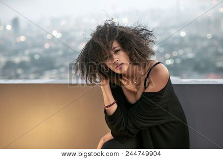 Sexy Curly Girl Is Posing With A Windy Hair On The Balcony On The Cityscape Background. She Wears Bl