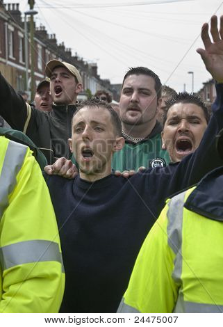 Plymouth Argyle fans shout at rival Exeter City Supporters as they are escorted by Police