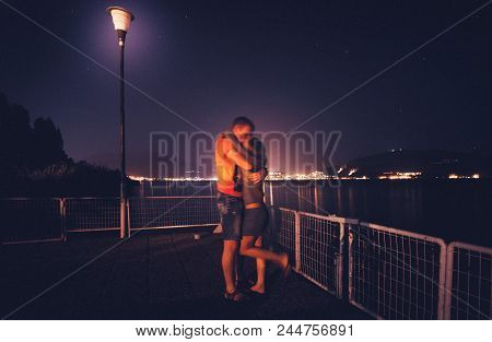 Romantic Couple Are Kissing In The Embankment Of Lake At Night And Lights Of City On The Background.