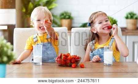 Happy Children Girl And Boy Brother And Sister Eating Strawberries With Milk