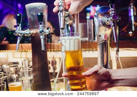 Young Woman Dispensing Beer In A Bar From Metal Spigots. Beautiful Female Bartender Tapping Beer In