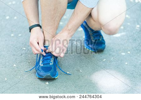 Getting Ready To Jogging. Hands Tying Shoelaces Sneaker, Road Background. Hands Of Sportsman With Pe